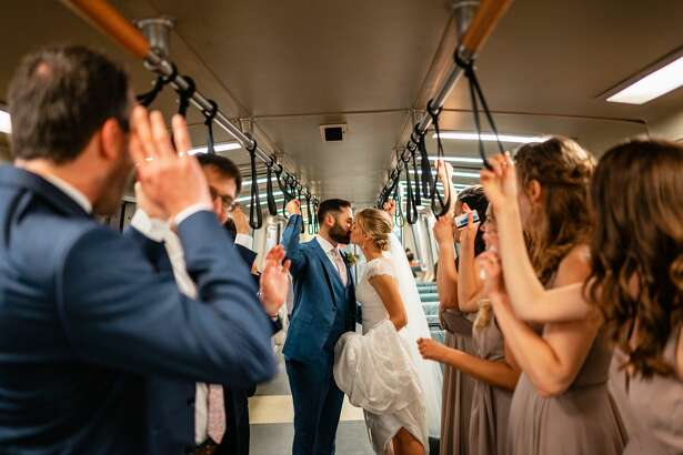 Laura Hansen and Jeremy Bachrach surrounded by their bridal party on a BART car on their July 13 wedding. The couple opted for public transit for their special day over a limousine or party bus.