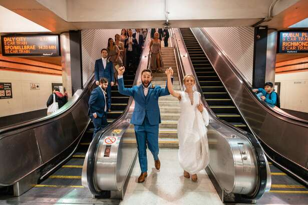 Laura Hansen and Jeremy Bachrach arrive at the platform of the Powell Street BART station on their wedding day. The couple opted for public transit for their special day over a limousine or party bus.