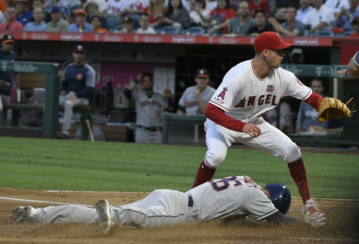 ANAHEIM, CA - JULY 15: Griffin Canning #47 of the Los Angeles Angels of Anaheim covers the plate as Myles Straw #26 of the Houston Astros scores as the result of a wild pitch in the second inning of the Los Angeles Angels of Anaheim at Angel Stadium of Anaheim on July 15, 2019 in Anaheim, California. (Photo by John McCoy/Getty Images)