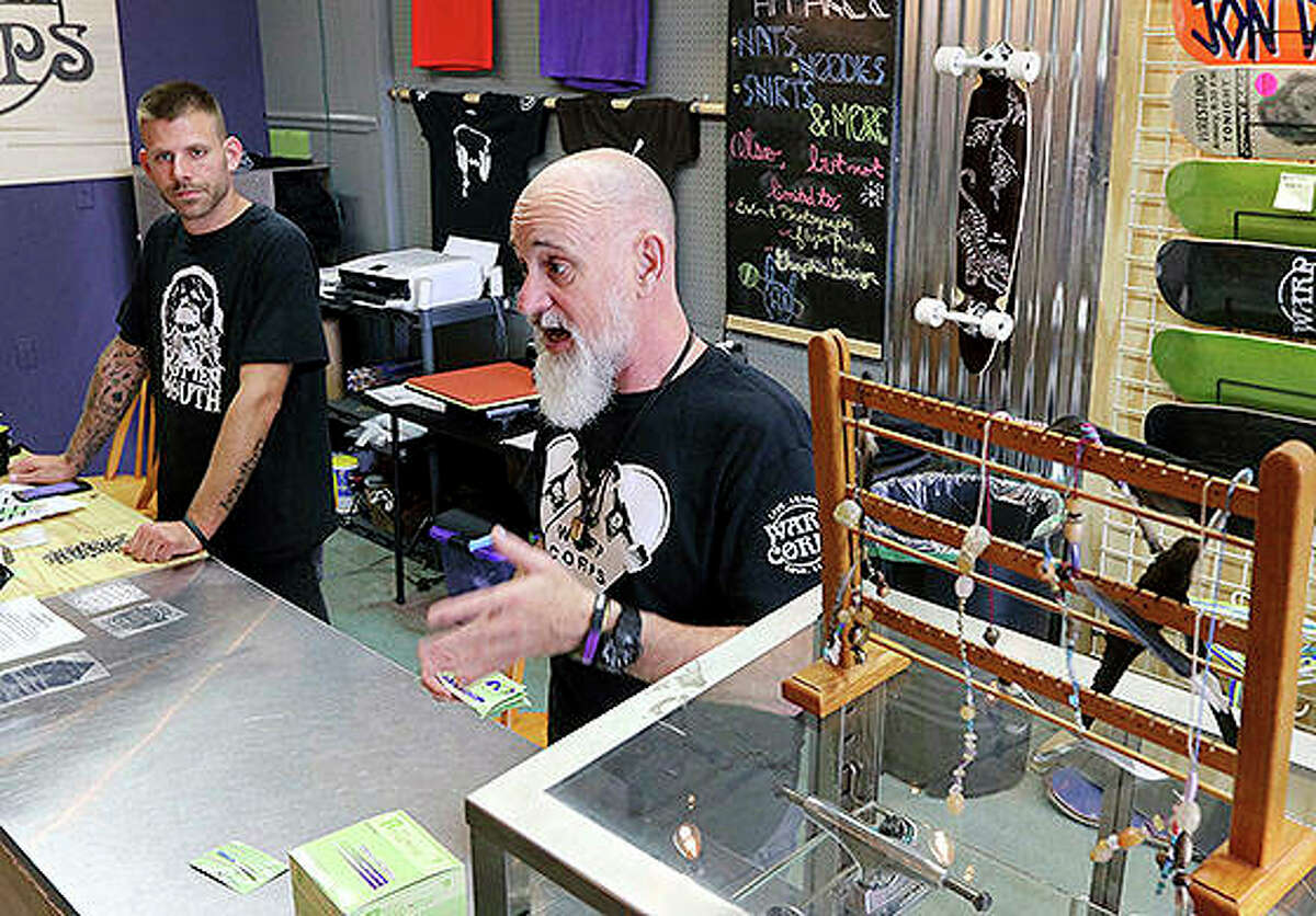 Co-owners Rob Mutert (front) and Mike Schoeler discuss the many facets their shop at Warp Corps in Woodstock. The new business on the historic Woodstock Square hosts support meetings and integrates an art gallery, clothing, skateboarding equipment, the Max Happy brand of coffee, music and more.