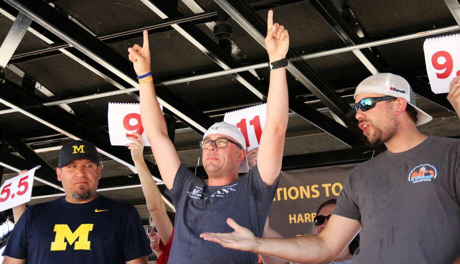 Kevin Soper (middle) celebrates winning the 2019 Maritime Hot Dog Eating Contest. He ate 11 of them, defending his hot dog eating championship that he won last year. Photo: Andrew Mullin/Huron Daily Tribune