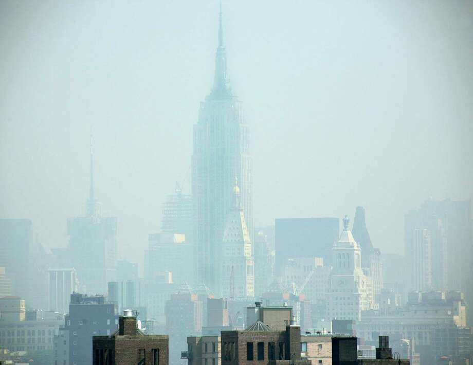 ** FILE ** Smog covers midtown Manhattan in New York in this July 10, 2007 file photo. Some of the biggest lobbying forces in Washington are waging an intense campaign to head off tougher regulations on smog that health experts blame for hundreds of premature deaths to asthma and other respiratory diseases. The EPA within weeks will decide whether it should further reduce the allowable amount of ozone, a precursor of smog, in the air. The tougher standard would require hundreds of counties across the country to find new ways to reduce the smog-causing emissions to meet the revised federal health standard. Groups representing manufacturers, automakers, electric utilities, grocers and cement makers, met with White House officials recently in a last ditch effort to keep the health standard unchanged. (AP Photo/Adam Rountree, File) Photo: Adam Rountree / AP / AP