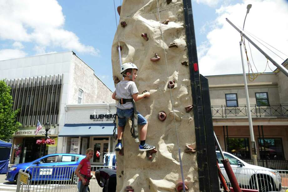 The New Canaan sidewalk sale on July 12-13 offered lots of activities for visitors. Cyprien Jacquet advanced up the rock climbing structure on the corner of Main Street and Elm Street. Photo: Grace Duffield / Hearst Connecticut Media / Connecticut Post