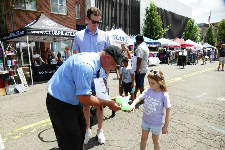 The New Canaan sidewalk sale on July 12, 2019, and July 13, 2019, offered lots of bargains and activities for visitors. Gary Sirico gave a balloon to London Dulmaine for her wrist. Photo: Grace Duffield / Hearst Connecticut Media / Connecticut Post