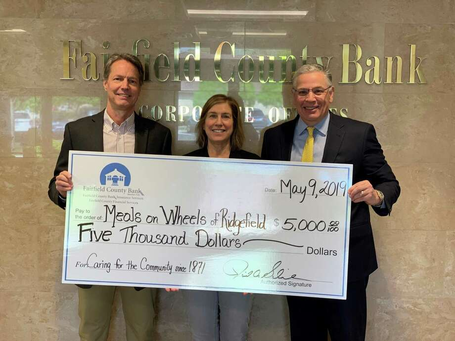 David Schneider, Chief Executive Officer of Fairfield County Bank, presents Dean Miller and Phyllis Appel, of Meals on Wheels of Ridgefield, with a $5,000 donation. Photo: Contributed Photo