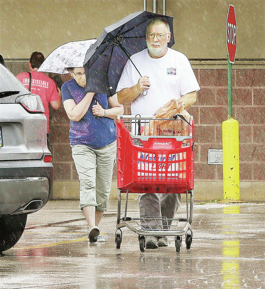 """As the Carpenters once said in a song, """"Rainy days and Mondays always get me down."""" This couple had both as they made a dash to their vehicle with their groceries in the pouring rain at the Alton Schnucks store in the 1700 block of Homer Adams Parkway in Alton. After more rain today, forecasts call for temperatures to skyrocket to the upper 90,s and near 100 degrees through Sunday."""