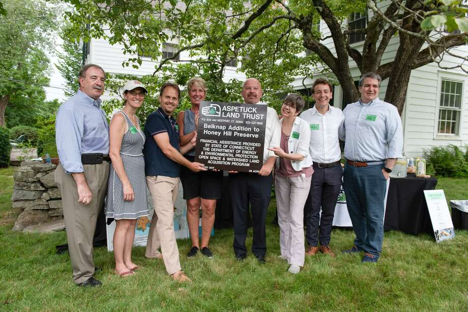The Aspetuck Land Trust presents a new sign for its Honey Hill preserve on the Weston-Wilton town line calling attention to the 38-acre Belknap Addition, adding to the preserve trail network and forest and wetland preservation area.  From left are: State Rep. Jonathan Steinberg (D-136 District - Westport),  State Rep. Cristin McCarthy Vahey (D-133 District - Fairfield), Dave Brant, executive director of the Aspetuck Land Trust, State Rep. Laura Devlin (D-134 District - Fairfield), State Rep. Joseph Gresko (D-121 District - Stratford), State Rep. Ann Hughes (D-135 District Easton, Redding, Weston), State Sen. Will Haskell (D-26 District - Bethel, New Canaan, Redding, Ridgefield, Weston, Westport, Wilton) and First Selectman Christopher Spaulding (D-Weston) Photo: Tracy Pennoyer /Contributed Photo