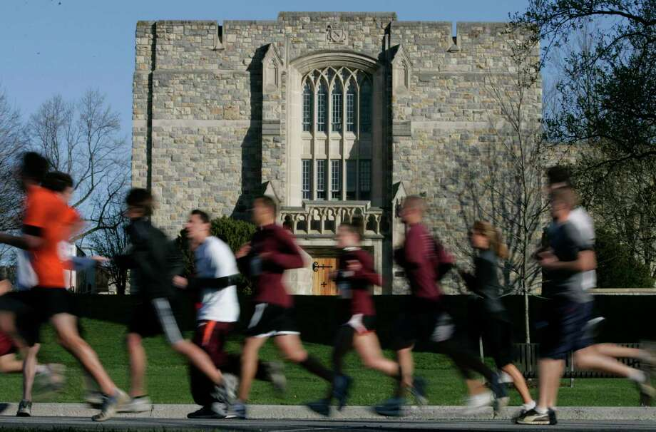 Runners run past Norris Hall at the start of a 3.2 mile run in honor of the 32 victims of the April 16, 2007 shootings at Virginia Tech on the campus of the school in Blacksburg, Va., Thursday, April 16, 2009. The run marked the start of the second anniversary activities. (AP Photo/Steve Helber) Photo: Steve Helber / ASSOCIATED PRESS / AP2009