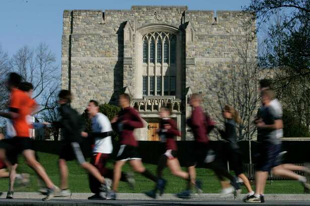 Runners run past Norris Hall at the start of a 3.2 mile run in honor of the 32 victims of the April 16, 2007 shootings at Virginia Tech on the campus of the school in Blacksburg, Va., Thursday, April 16, 2009. The run marked the start of the second anniversary activities. (AP Photo/Steve Helber)