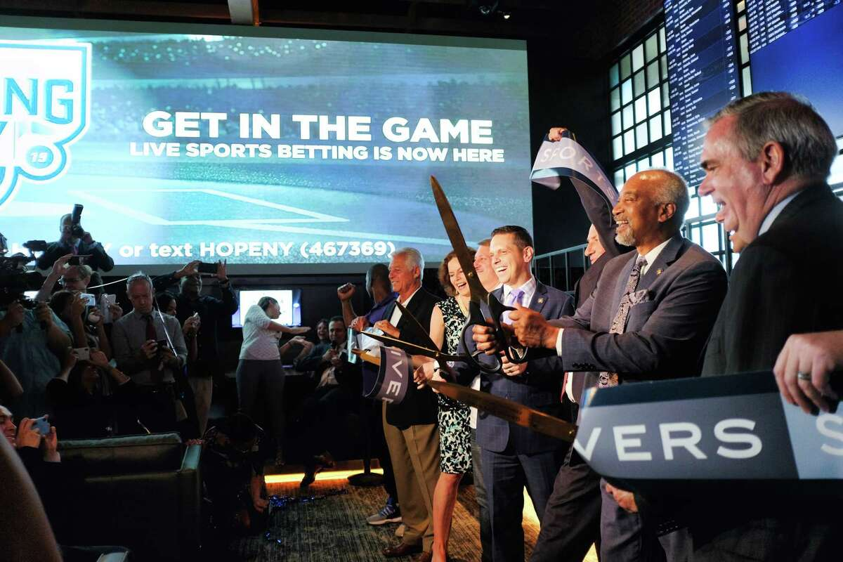 Schenectady Mayor Gary McCarthy, right, State Assemblymember Gary Pretlow, Chair of the Assembly Racing, Gaming, and Wagering Committee, second from right, Assemblymember Angelo Santabarbara, third from right and other elected officials and gaming business representatives take part in a ribbon cutting ceremony on opening day at the Rivers Sportsbook on Tuesday, July 16, 2019, in Schenectady, N.Y. (Paul Buckowski/Times Union)