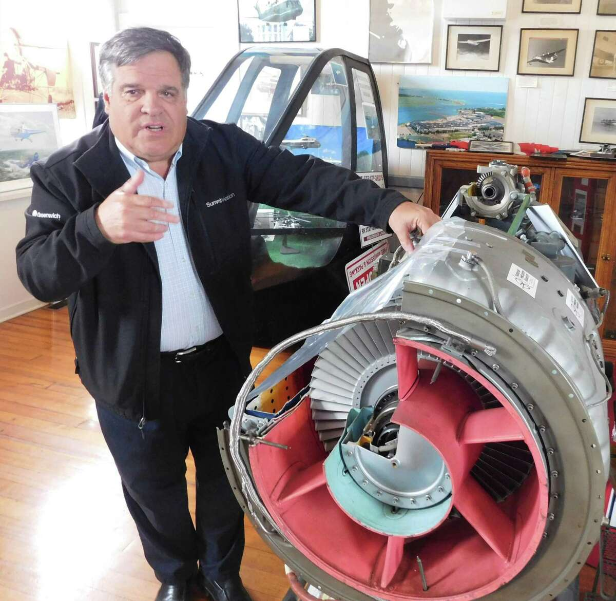 National Helicopter Museum board president Ken Pike explains the Stratford-based museum's mission while standing next to a displayed helicopter engine.