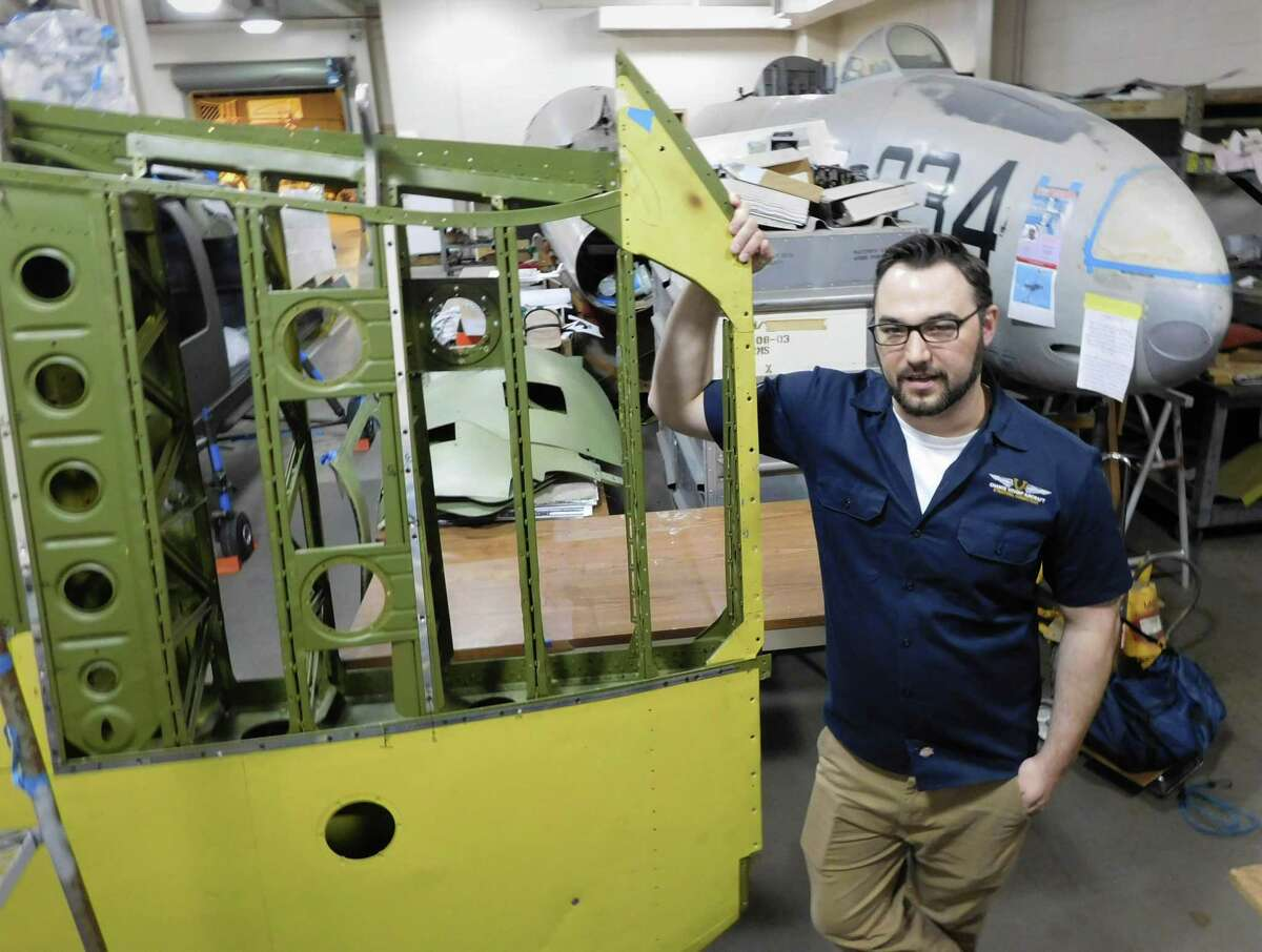 Chris Soltis, curator and exhibit designer at the Connecticut Air & Space Center in Stratford, holds a wing being restored for a World War II Corsair fighter plane.