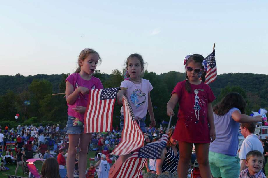 From left to right: Emma, Camila, and Ali wave the American flag during the town's annual Fourth of July celebration at Ridgefield High School last week. Photo: Stephen Coulter / Hearst Connecticut Media