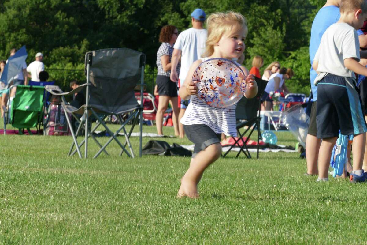 Kiera, 3, plays with a Frisbee during the annual Fourth of July celebration at Ridgefield High School last week.
