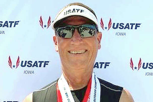Mike Young of Wood River wears the second- and third-place medals he captured at last week's USATF Masters Track and Field Championships in Ames, Iowa.