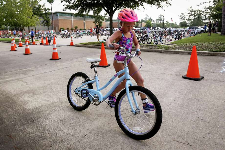 About 275 kids are set to swim, bike and run this Saturday in the sold-out The Woodlands Family YMCA at Branch Crossing's annual Kids Triathlon—some are even on a wait list hoping to enter the event, which has been turning kids ages 6 to 12 into triathletes for more than 15 years. Here, Kaia Finanger, 7, mounts her bike during the YMCA Kids Triathlon on Saturday, July 21, 2018, at The Woodlands Family YMCA. Photo: Michael Minasi, Staff Photographer / Houston Chronicle / © 2018 Houston Chronicle