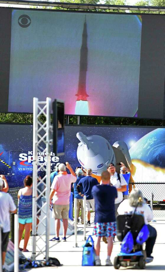 People watch lift-off during the Apollo 11 Launch Flashback, broadcast by CBS at the Kennedy Space Center's Apollo/Saturn V exhibit, Tuesday July 16, 2019. Guests viewed a rebroadcast of the 1969 launch from the grandstands at the Banana Creek viewing area to commemorate the launch of the Saturn V rocket and the Apollo 11 crew 50 years ago. (Joe Burbank/Orlando Sentinel via AP) Photo: Joe Burbank / Associated Press / Orlando Sentinel
