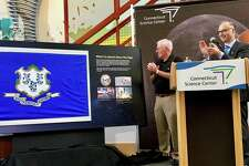 On Tuesday, exactly 50 years after the launch of the Apollo 11 mission to the moon, the Connecticut Science Center in Hartford celebrated by unveiling a Connecticut flag that flew aboard the space shuttle Atlantis to the International Space Station, with two astronauts from the state -- Rick Mastracchio of Waterbury and Dan Burbank of Tolland, who donated the flag. Pictured is Ed O'Connor, a retired engineer from United Technologies Corp. who worked on space systems with Hamilton Sundstrand, now part of UTC's Collins Aerospace unit.  O'Connor is shown with Matt Fleury, CEO of the science center, and with Amanda Dokas, an intern there.