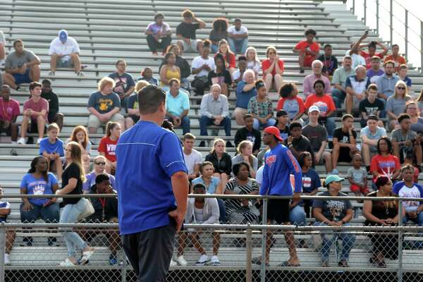 West Brook football coach Eric Peevey addresses a crowd who met at Durley Stadium during Sunday's prayer service for the four Bruin football players injured in a car wreck this weekend. Photo taken Sunday, 7/14/19