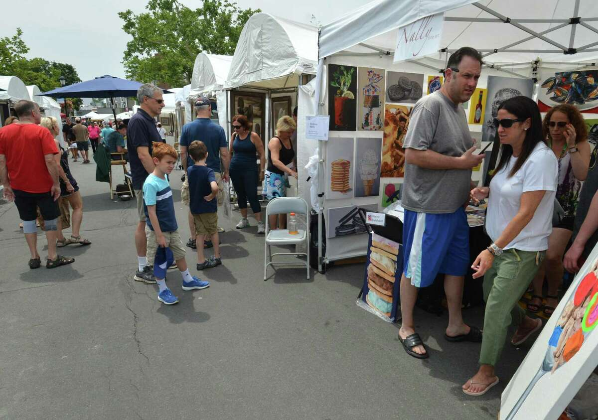 The 46th Westport Fine Arts Festival returns to downtown July 20 and 21. The free event features artists, local restaurants, live music and creative art activities. Pictured are visitors to last year's event.