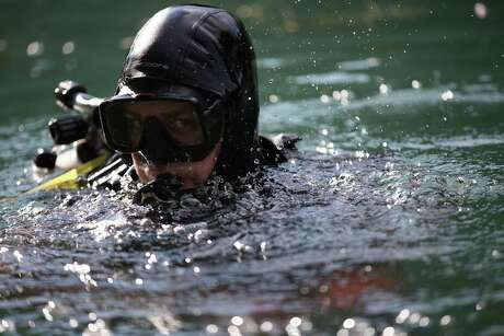 Chris Young emerges from the Comal River in New Braunfels after a recent dive. The water world version of St. Anthony of Padua, the patron saint of lost things, Young patrols the Comal, Guadalupe and San Marcos rivers in search of iPhones, wedding rings, sunglasses and other valuables accidentally dropped into the murky drink.
