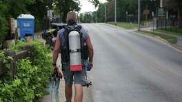 Chris Young walks back to his truck after searching a mile-long length of the Comal River one morning recently.