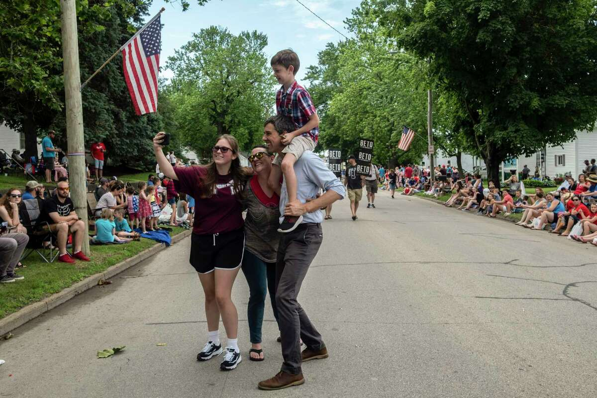 Beto O'Rourke, a Democratic candidate for president, carries his son Henry on his shoulders while greeting people and walking in the4th of July parade in Independence, Iowa, July 4, 2019. (Jordan Gale/The New York Times)