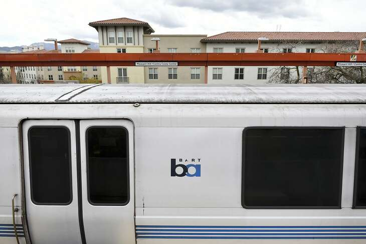 A train stops on the platform at the Pleasant Hill BART Station as the Avalon Walnut Creek Apartments, part of the   Contra Costa Centre, are seen in the background, in Walnut Creek, CA, on Friday March 2, 2018.