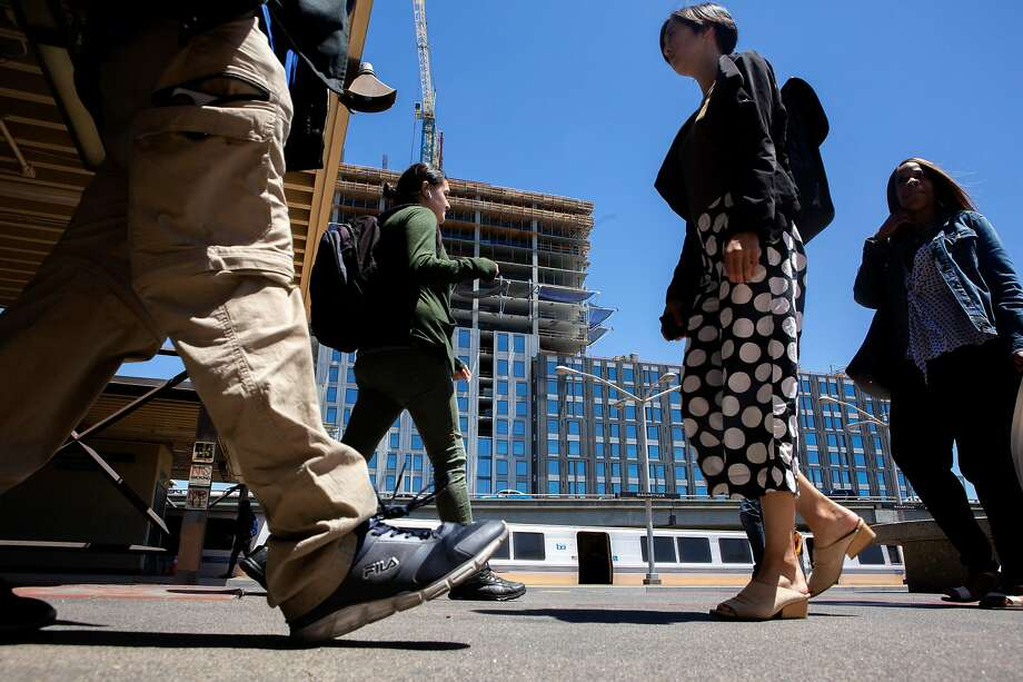 People make their way at MacArthur BART Station in Oakland where a 24-story apartment tower is scheduled to open next year. Photo: Santiago Mejia / The Chronicle