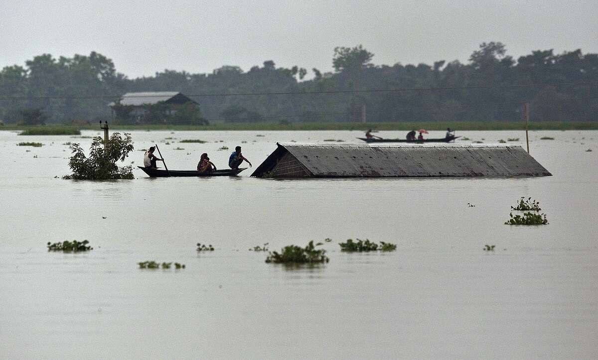 Flood affected villagers travel on boats near a submerged house in Burha Burhi village east of Gauhati India, Monday, July 15, 2019. After causing flooding and landslides in Nepal, three rivers are overflowing in northeastern India and submerging parts of the region, affecting the lives of more than 2 million, officials said Monday.(AP Photo/Anupam Nath)