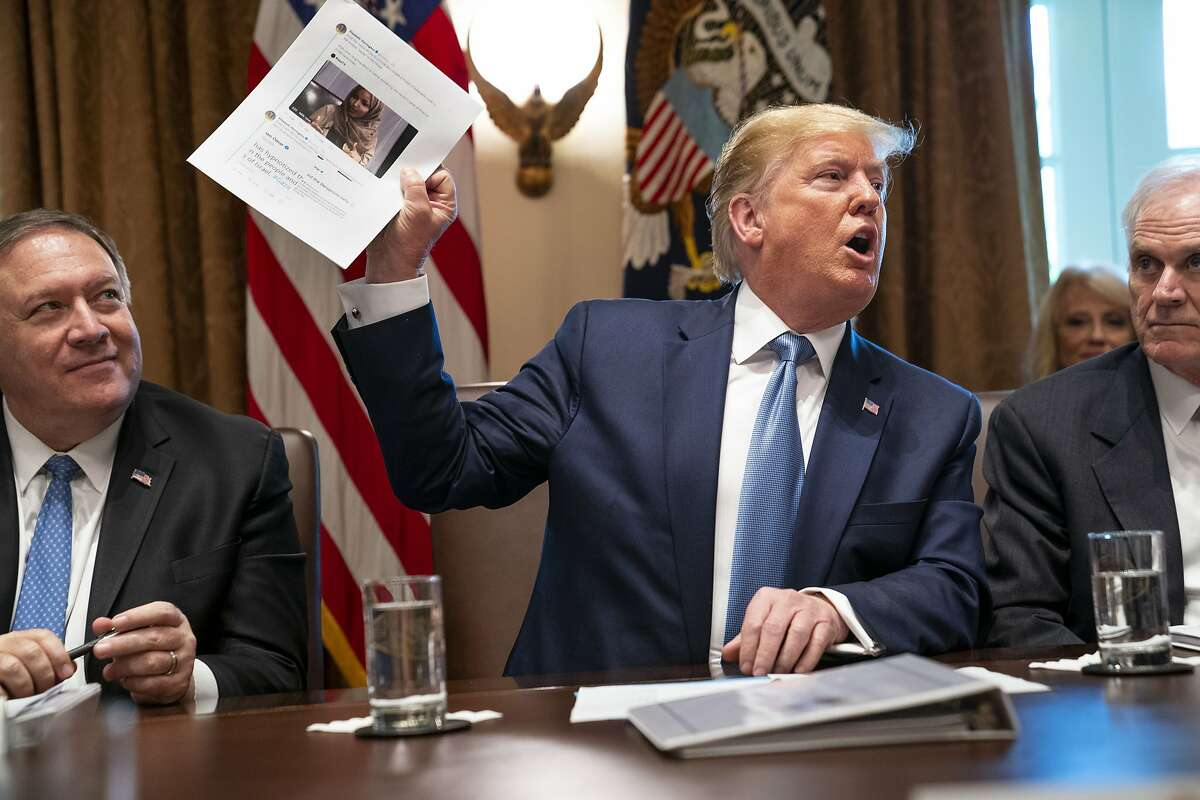 President Donald Trump holds up a photo of Rep. Ilhan Omar (D-Minn.) during a meeting at the White House in Washington on Tuesday, July 16, 2019. Trump denied that his tweets suggesting that Omar and three other minority congresswomen leave the country were racist, and implored House Republicans to reject a resolution up for a Tuesday evening vote that condemns his statements. (Doug Mills/The New York Times)
