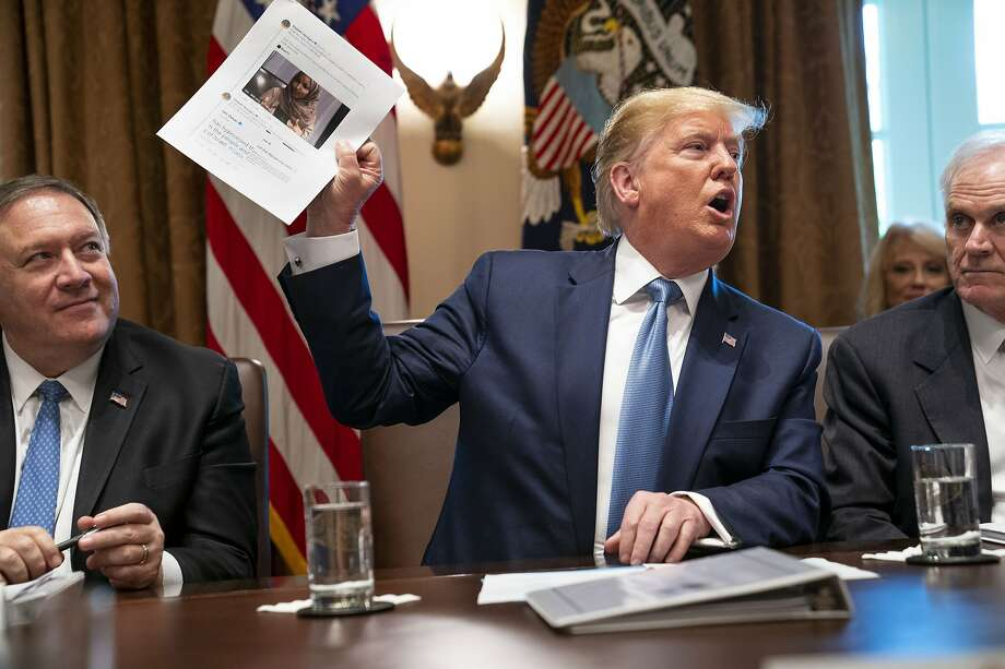 President Trump holds up a photo of Rep. Ilhan Omar. He denied that his tweets suggesting the congresswoman leave the country were racist. Photo: Doug Mills / New York Times