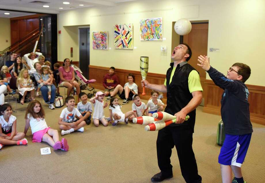 "Jason Pipitone bounces a ball on his head while Bennett Lutkins, 10, of Camp Hill, Pa., helps with his act during the ""Juggling and Magic with Jason"" performance at the Byram Shubert Library in the Byram section of Greenwich, Conn. Monday, June 15, 2019. Pipitone entertained and incorporated the audience into his impressive juggling feats, magic tricks, and slapstick comedy. Photo: Tyler Sizemore / Hearst Connecticut Media / Greenwich Time"