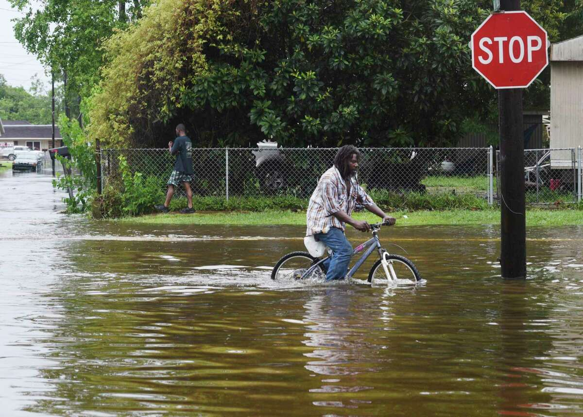 A man tries to bike through the flooding from the rains of storm Barry on LA Hwy 675 in New Iberia, La., Sunday, July 14, 2019. Tropical Depression Barry dumped rain as it slowly swept inland through Gulf Coast states Sunday. (Henrietta Wildsmith/The Shreveport Times via AP)