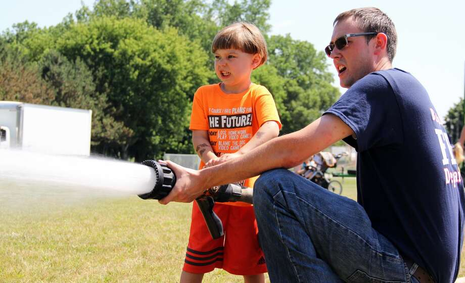 Junior firefighter Michel Scoviac, left, helps a Bingham Township fireman get a grip on the fire hose and spray the lawn on Saturday. Children had the opportunity to help operate a fire hose during one of the many activities offered throughout Ubly's Homecoming celebration. Photo: Andrew Mullin/Huron Daily Tribune