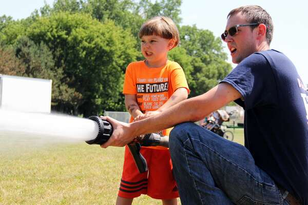 Junior firefighter Michel Scoviac, left, helps a Bingham Township fireman get a grip on the fire hose and spray the lawn on Saturday. Children had the opportunity to help operate a fire hose during one of the many activities offered throughout Ubly's Homecoming celebration.