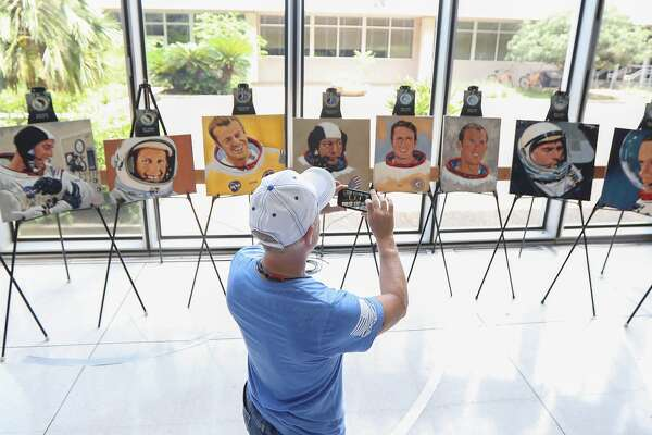 """Mike Surber takes a photo of Logan Goodson's """"The Moon Walkers"""" art display during an event commemorating the launch of Apollo 11 Tuesday, July 16, 2019, in Houston."""