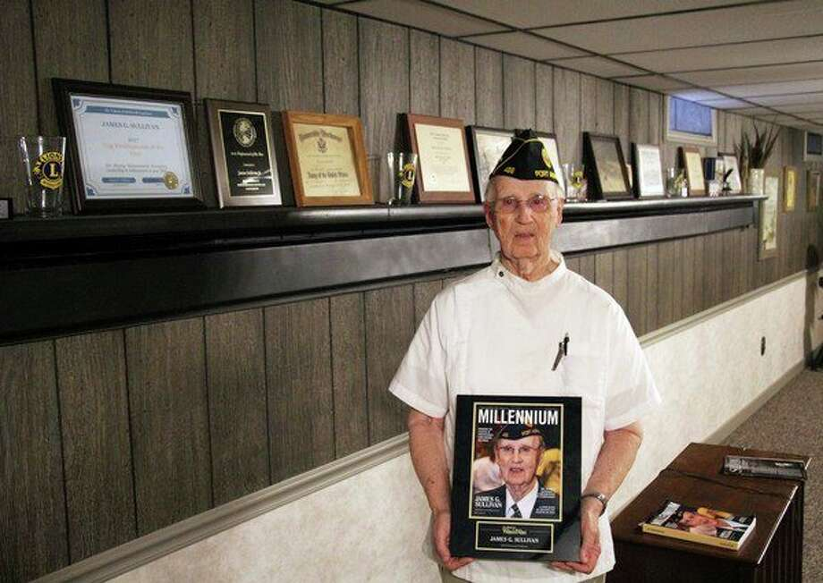 James Sullivan, owner of Jerry's Barber Shop, poses in his home with a plaque commemorating his cover photo on the business magazine Millennium. (Seth Stapleton/Huron Daily Tribune)