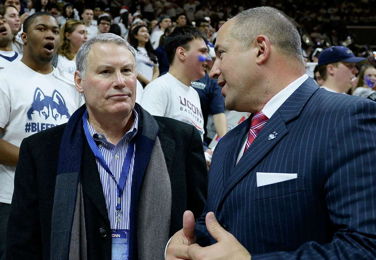 In this Feb. 13, 2017, file photo, American Athletic Conference commissioner Mike Aresco, left, talks with UConn athletic director David Benedict, right, before an NCAA college basketball game between UConn and South Carolina in Storrs.