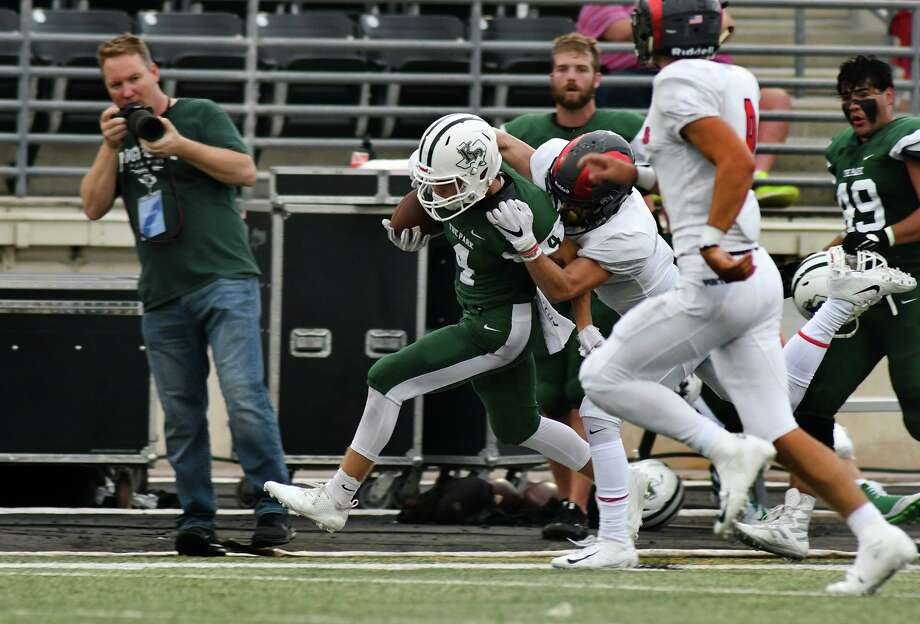 Kingwood Park junior wide receiver Canen Adrian (4) tries to break the grasp of a Porter defender on a pass play in the first quarter of their District 9-5A matchup at Turner Stadium in Humble on Sept. 29, 2018. Photo: Jerry Baker, Houston Chronicle / Contributor / Houston Chronicle