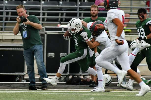 Kingwood Park junior wide receiver Canen Adrian (4) tries to break the grasp of a Porter defender on a pass play in the first quarter of their District 9-5A matchup at Turner Stadium in Humble on Sept. 29, 2018.