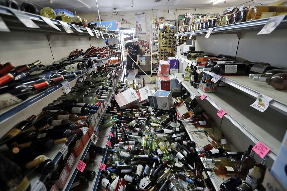 Bottles of wine are strewn in an aisle as Victor Abdullatif (background center) mops up inside a market in Ridgecrest. Photo: Marcio Jose Sanchez / Associated Press