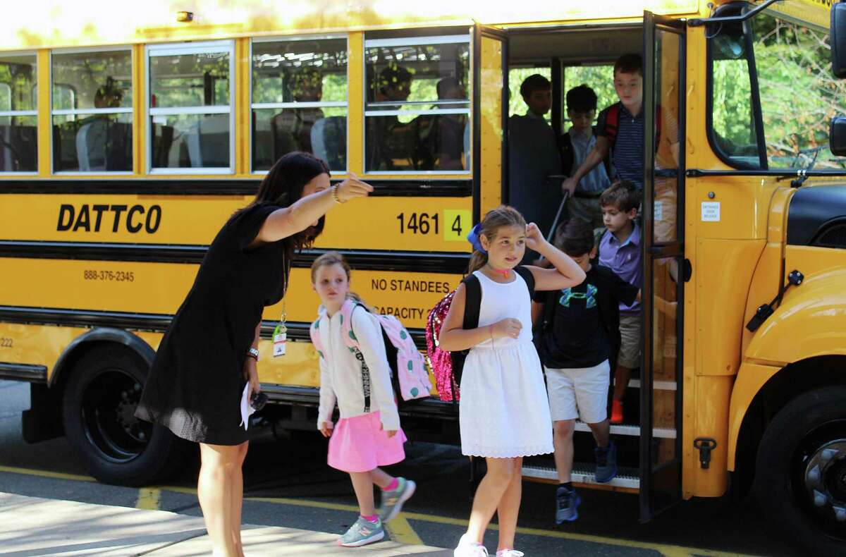 West School Assistant Principal Ashley Furnari directs students off the bus on a previous first day of school in New Canaan, following the students' summer. Twelve kids, such as some shown coming off of this one, on a 72-person bus makes New Canaan school officials fear the document rules for operating summer schools during COVID-19.