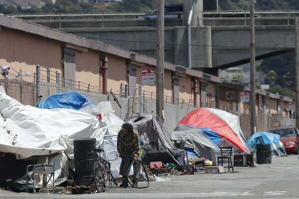 This Thursday, June 27, 2019, photo shows a man holding a bicycle tire outside of a tent along a street in San Francisco. A federally mandated count of homeless in San Francisco increased 17% in two years, driven in part by a surge of people living in RVs and other vehicles.