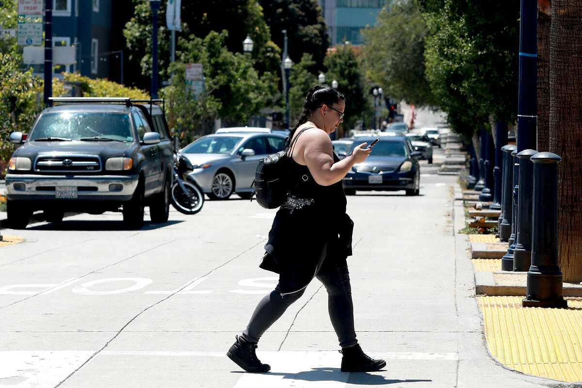 Pedestrians cross the street at the corner of Octavia and Hayes at Patricia's Green in Hayes Valley in San Francisco, Calif., on Tuesday, July 16, 2019. SFMTA board will vote Tuesday on whether to ban cars from a block of Octavia Street near Patricia's Green in Hayes Valley, which could become a new model for public space in the city. Proponents say that recycling roadways as plazas is the best way to make San Francisco's wealthy enclaves more inclusive and family-friendly.