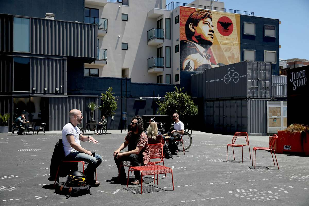 Folks hang out near Juice Shop at the corner of Octavia and Hayes at Patricia's Green in Hayes Valley in San Francisco, Calif., on Tuesday, July 16, 2019. SFMTA board will vote Tuesday on whether to ban cars from a block of Octavia Street near Patricia's Green in Hayes Valley, which could become a new model for public space in the city. Proponents say that recycling roadways as plazas is the best way to make San Francisco's wealthy enclaves more inclusive and family-friendly.