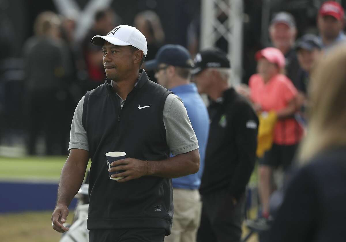 Tiger Woods of the United States holds a drink as he walks through the practice range ahead of the start of the British Open golf championships at Royal Portrush in Northern Ireland, Tuesday, July 16, 2019. The British Open starts Thursday. (AP Photo/Jon Super)