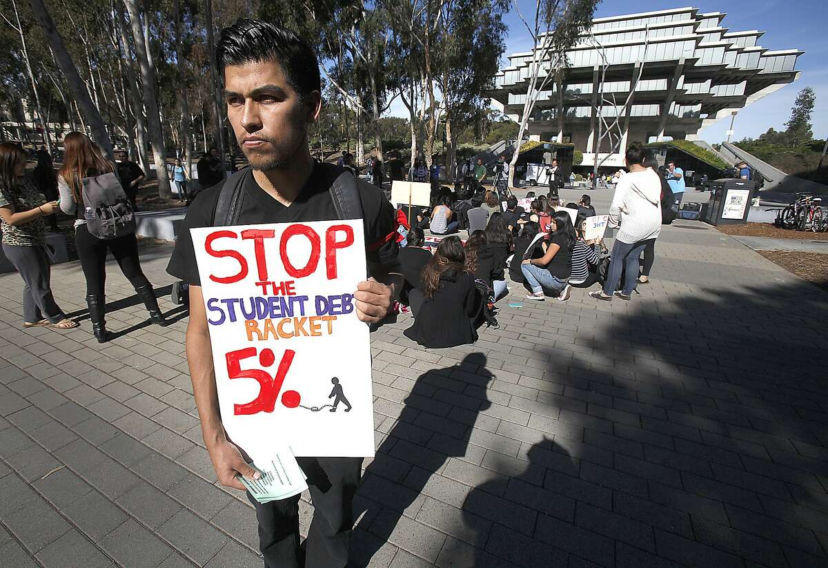 Several hundred University of California San Diego students gathered on the walkway in front of Geisel Library in a sit-in to protest a proposed hike in tuition of up to five percent for the next five years Tuesday Nov. 18, 2014. Andrew Villalobos carries a sign prior to a sti-in of UCSD students. A senior graduating with a B.S. in engineering, he is worried about his brother and sister, both in high school and what this might mean for them if they choose to attend a UC school. (AP Photo/The U-T San Diego, John Gastaldo}