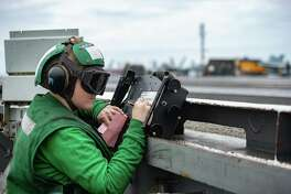 Aviation Boatswain's Mate (Equipment) 3rd Class Megan May, from Midland, Texas, records aircraft weight on the flight deck aboard the Navy's forward-deployed aircraft carrier USS Ronald Reagan (CVN 76) during flight operations.
