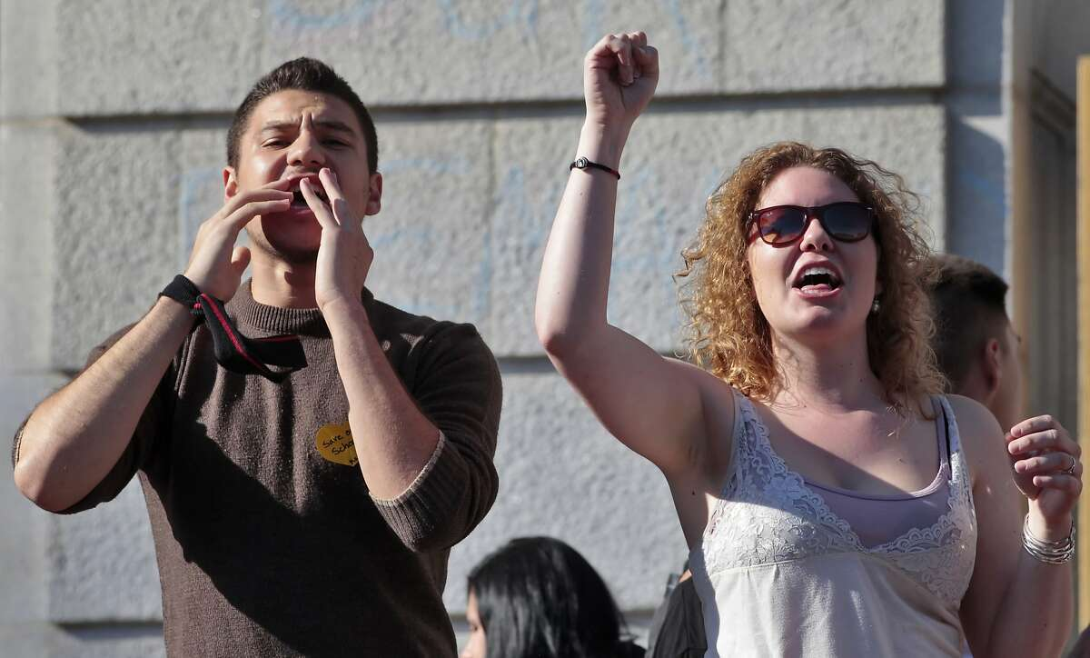 Marco Amaral and Taylor Kohles cheer the crowd outside to support the students from UC Berkeley who chained themselves together and to Wheeler Hall, Thursday, March 3, 2011, in protest of tuition rate hikes, in Berkeley, Calif.